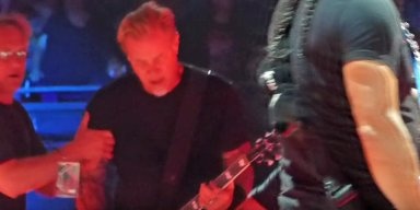 METALLICA's JAMES HETFIELD Falls On Stage At Amsterdam Concert, continues playing the track while grimacing in pain.