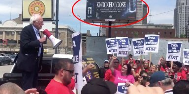 "Bernie Sanders Ralley in Front of a ""Knocked Loose"" Billboard"